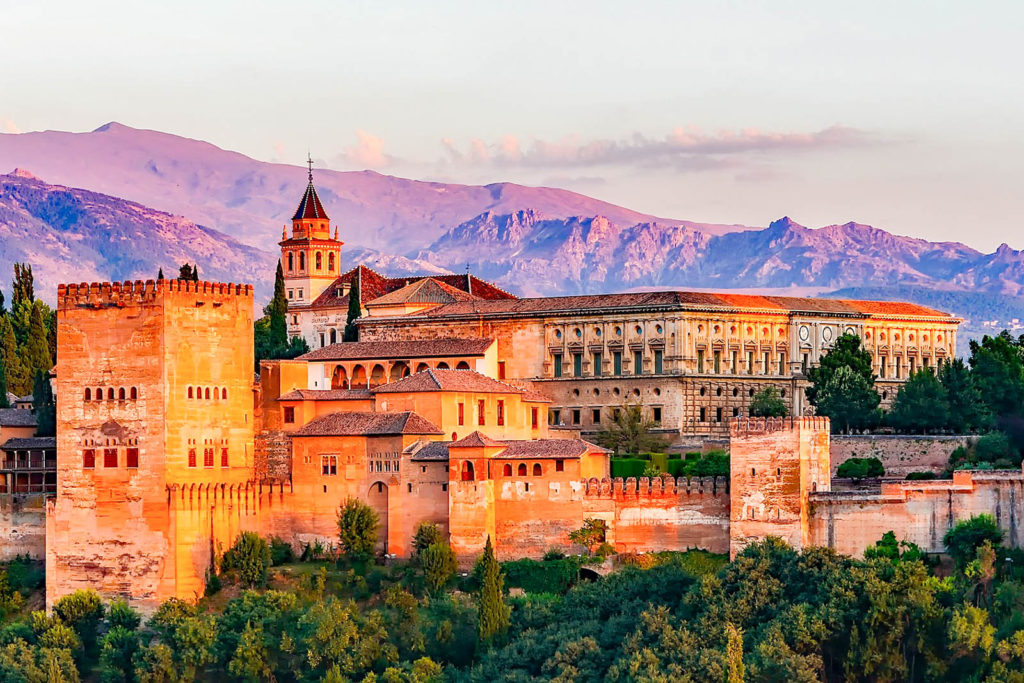 View of the Alhambra Palace in Granada with the sun setting in the background