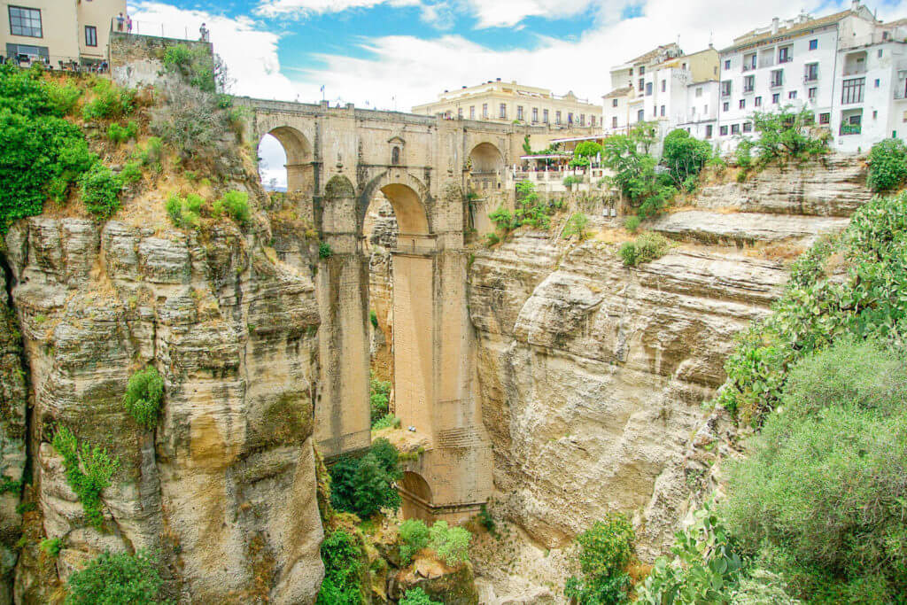 Photo of Puente Nuevo in Ronda, Spain, showing the bridge and surrounding white buildings as well as the bridge height