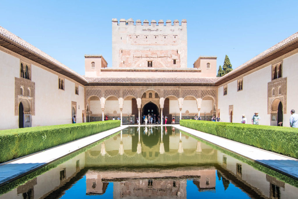 The front façade of the Alhambra in Granada, with the building's reflection in the pool directly in front of it.