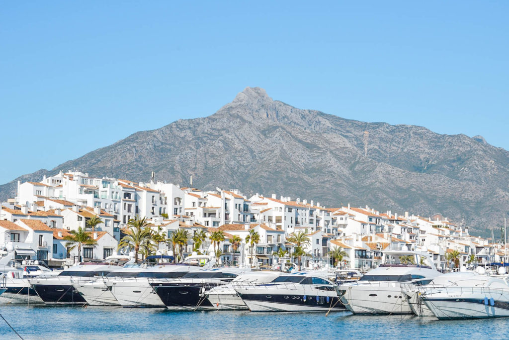 A view of Puerto Banús in Marbella, with various yachts docked in the ocean.