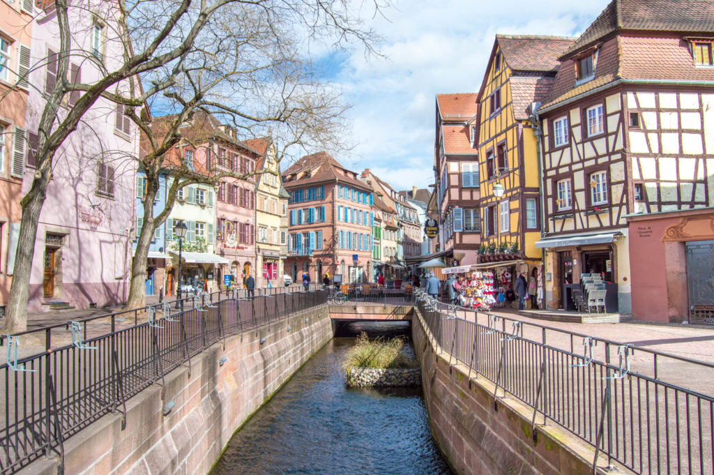 A view of one of the canals in Colmar, with colorful buildings surrounding it on both sides.