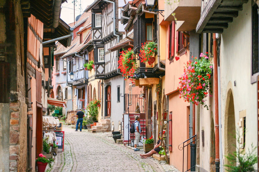 A colorful street in Eguisheim, Alsace, with flowers hanging off colorful timbered homes.