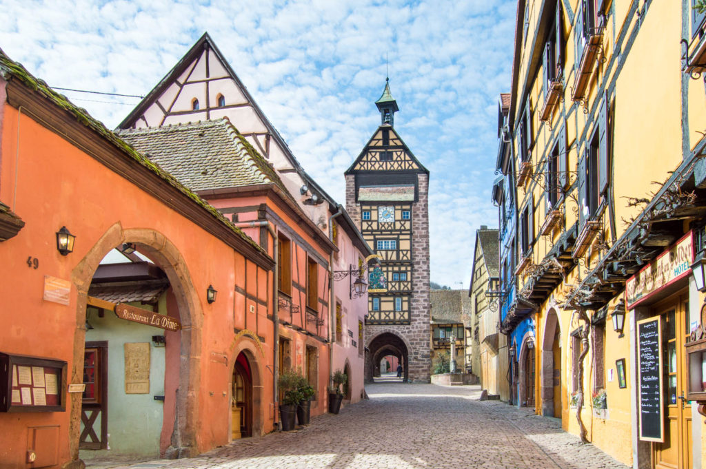 One of the main roads in Riquewihr, with colorful buildings on both sides and a clock tower.